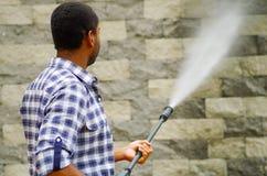 Man wearing square pattern blue and white shirt holding high pressure water gun, pointing towards grey brick wall Stock Photo