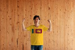 Man wearing Sri Lanka flag color of shirt and standing with raised both fist on the wooden wall background. Four color of green orange yellow and dark red with royalty free stock images