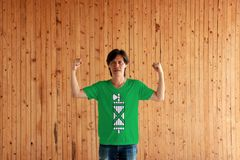 Man wearing St. Gallen flag color of shirt and standing with raised both fist on the wooden wall background. The canton of Switzerland Confederation stock photography