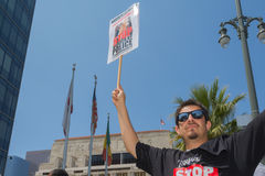 Man wearing stop murder by police shirt and holding sign Royalty Free Stock Photo
