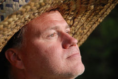 Man wearing straw hat. Man wearing woven straw hat looks into the sun royalty free stock photos