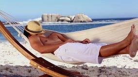 Man wearing straw hat relaxing in a hammock stock video