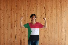 Man wearing Sudan flag color of shirt and standing with raised both fist on the wooden wall background. Red white and black; with a green triangle based at the stock images