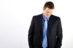 Man Wearing Suit. A young man is wearing a business suit with a blue tie, and is looking down at the floor.  Horizontally framed shot Stock Images