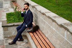 Man wearing suit chatting on phone on the street. Stock Photography