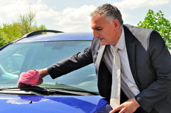 Man wearing suit cleaning a car. Royalty Free Stock Image