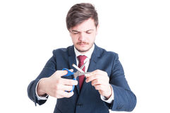 Man wearing suit cutting cigarettes with eyes closed Royalty Free Stock Photos