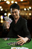 A man wearing a suit holding Hearts Suit Straight Flush stock photo