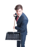 Man wearing suit holding snow shovel looking mad Stock Image