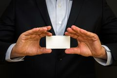 Man wearing a suit holding white business card on black wall background. Mock up, space for text royalty free stock images