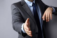 Man wearing a suit offering to shake hands Stock Image