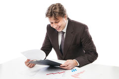 Man wearing suit sitting in desk observing charts Stock Images