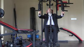 Man wearing suit and tie training with strength machine at gym. UHD 4K stock footage