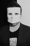 Man wearing a suit and white masquerade mask Royalty Free Stock Images