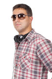 Man wearing sunglasses with headphones around her neck Stock Image