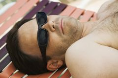 Man wearing sunglasses lying on sunlounger. Royalty Free Stock Photos