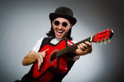 Man wearing sunglasses and playing guitar Stock Photos