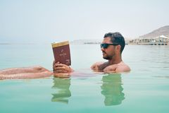 Man Wearing Sunglasses Reading Book on Body of Water stock photo