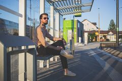 Man Wearing Sunglasses Sitting at Bus Stop during Daytime Royalty Free Stock Photos