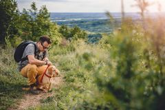 Man with a dog resting at the hiking trail. Man wearing sunglasses with a small yellow dog resting at the hiking trail royalty free stock photo