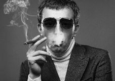Man wearing sunglasses and smoking a cigerette. Royalty Free Stock Photography
