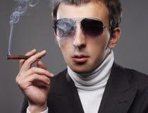 Man wearing sunglasses and smoking a cigerette. Stock Photo