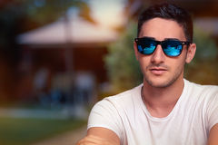 Man Wearing Sunglasses Waiting in a Restaurant. Portrait of a handsome with sport style sunglasses with mirror lenses Royalty Free Stock Photo