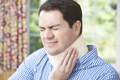Man Wearing Surgical Collar In Pain. Man Wearing Surgical Collar Grimacing In Pain Stock Images