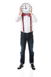 Man wearing suspenders hiding behind big clock. Royalty Free Stock Photography