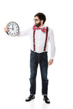 Man wearing suspenders holding big clock. Stock Photo