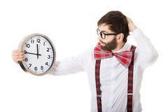 Man wearing suspenders holding big clock. Royalty Free Stock Image