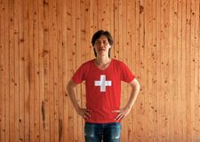 Man wearing Switzerland flag color shirt and standing with akimbo on the wooden wall background. Red flag with a white cross in the centre royalty free stock image