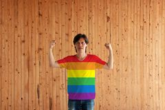 Man wearing symbol color of LGBTQ+ shirt and standing with raised both fist on the wooden wall background. The concept of lgbtq community royalty free stock images