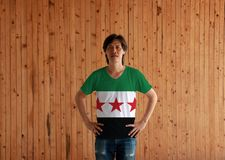 Man wearing Syrian Interim Government flag color shirt and standing with akimbo on the wooden wall background. Tricolor of green white and black with three red stock images