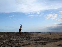 Man wearing a t-shirt, shorts, and slippers Handstands on shore Royalty Free Stock Photography