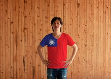 Man wearing Taiwan flag color shirt and standing with akimbo on the wooden wall background. A red field with a navy blue canton bearing a white sun with 12 royalty free stock photos