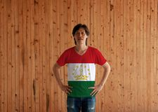 Man wearing Tajikistan flag color shirt and standing with akimbo on the wooden wall background. Red white and green with a crown and seven stars on top stock images