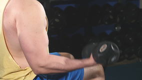Man wearing tank top sits doing left arm curls with dumbbells during weight lifting routine stock video