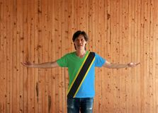 Man wearing Tanzania flag color shirt and standing with arms wide open on the wooden wall background stock photo