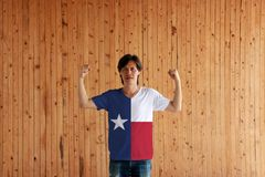 Man wearing Texas color of shirt and standing with raised both fist on the wooden wall background. The states of America stock image