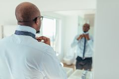Man wearing a tie. Man putting on a tie looking at a mirror. Back view of a businessman wearing a neck tie royalty free stock image