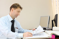 Man wearing tie sits in office of realtor and looks drawings Stock Photo