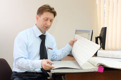 Man wearing tie sits in office of realtor and looks samples Stock Photos