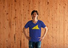Man wearing Tokelau flag color shirt and standing with akimbo on the wooden wall background. A light blue field with the large yellow disk shifted royalty free stock images