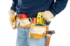Man wearing tool belt. A skilled tradesman stands with his fully loaded tool belt ready to work. Isolated on white for designer convenience royalty free stock images