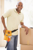 Man wearing tool belt by boxes in new home Royalty Free Stock Photography