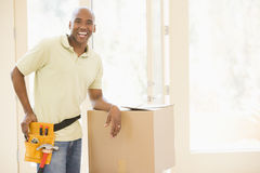 Man wearing tool belt by boxes in new home Stock Image