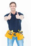 Man wearing tool belt while showing thumbs up sign. Portrait of confident man wearing tool belt while showing thumbs up sign over white background stock image