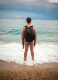 Man wearing tourist backpack standing on sea shore Stock Images