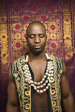 Man wearing traditional African clothing. Portrait of African-American mid-adult man wearing embroidered African vest and beads Royalty Free Stock Photo